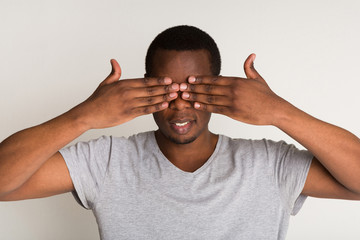 Pencive black man covering eyes with hands