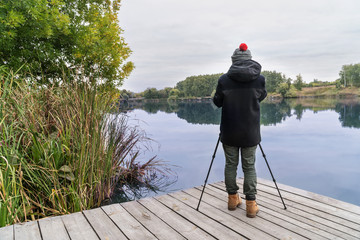 Photographer takes a picture of a beautiful lake by putting a camera on a tripod. Back view