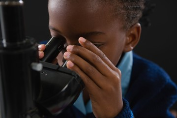 Schoolgirl using microscope against black background