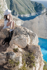 Woman sitting on the cliff at Navagio bech