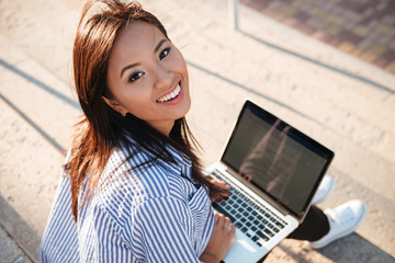 Top view of young cheerful asian woman, holding laptop on her lap, looking at camera, outdoor
