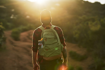 male millennial hiker trekking up trail in southern california during sunset Wall mural