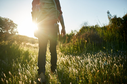 male millennial hiker walking through grass in southern california during sunset