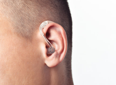 Young man hearing impaired dressing the hearing aid. At isolated white background.