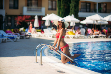 A beautiful girl in a pink bathing suit sunbathing by the swimming pool .Sunny weather. Summer