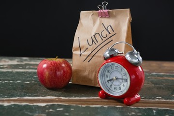 Apple, alarm clock and lunch bag on wooden table