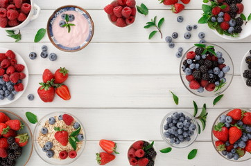 Healthy breakfast with berries and yogurt on white wooden table
