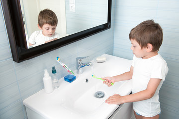 cute small child washing his toothbrush under stream of water in bathroom