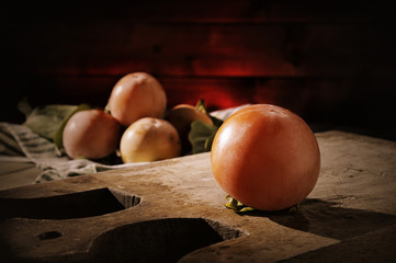 Fresh persimmons freshly picked on an old wooden table