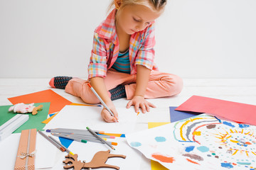 Early childhood education. Artistic child. Pensive baby girl on white background, christmas colorful drawing, creativity concept