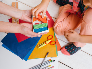 Early child education. Creative art family. Unrecognizable girls teamwork top view, colorful work process on wooden background, creativity concept