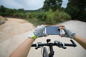 cyclist use smatphone taking photo on mountain trail