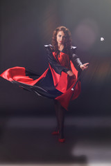 Young beautiful woman in cloak of red and black fabric wearing red heels in one hand holds cane, while the other is waving the hem of a raincoat in iridescent light against a dark background