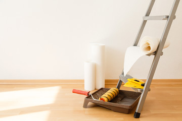 Tools for gluing wallpapers. A room after renovation. Fresh repair in a room. Floor from laminate