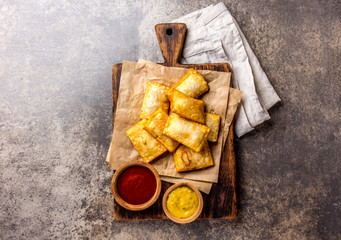 Fried cheese empanadas. Traditional Latin American snack served on wooden board with chili sauce and mustard. Top view, stone background