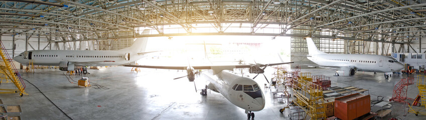 Three passenger aircraft in a hangar with an open gate for service, view of the panorama.