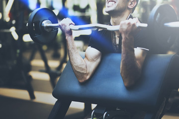 Muscular bodybuilder guy doing exercises with big dumbbell in gym