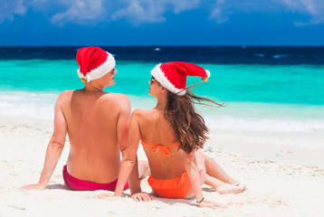 young couple in santa hats having fun on tropical beach. new year,