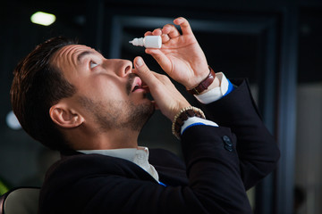 Office worker suffering dry eye syndrome, artificial tears eye drops, tired businessman
