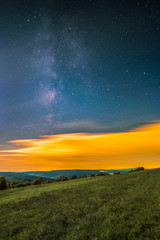 Landscape with the Milky Way as seen from the mountain Katzenbuckel in the Odenwald in Germany.