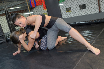 2 female friends wrestling a the gym