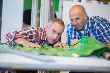 Men examining unrolled plastic product