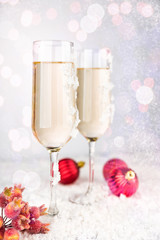 Two champagne glasses on light bokeh background. New Year and Christmas Celebration. Red baubles, berries, garland, tree ornaments and gift boxes