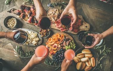 Photo sur Plexiglas Assortiment Flat-lay of friends eating and drinking together. Top view of people having party, gathering, dinner together sitting at wooden rustic table set with wine snacks and fingerfoods. Hands with glasses