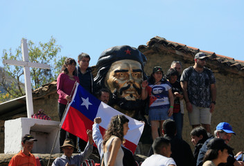 Chilean supporters pose on a statue of Ernesto Che Guevara in La Higuera where he was executed, during an event to commemorate Che Guevara's 50th death anniversary
