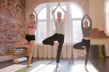 Girls gymnastics. Teenage yoga class. Children workout together with female instructor, gym bright background. Healthy family lifestyle, stretching exercise