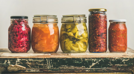 Autumn seasonal pickled or fermented vegetables in jars placed in row over vintage kitchen drawer, white wall background, copy space. Fall home food preserving or canning