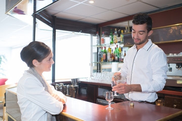 waiter serving a cocktail to woman at bar counter