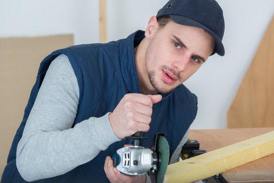carpenter sanding a wood with sander