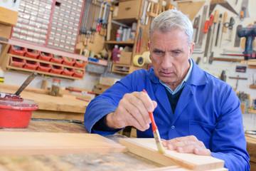 senior craftsman brushing in hand planed boards