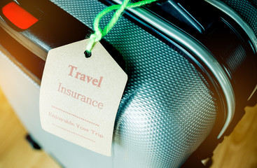Travel Insurance tag on Suitcase safety with letters enjoyable your trip on bag light blurred background, that is intended cover medical expenses, trip cancellation or flight accident.