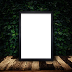 Mockup of black frame poster on green ivy wall background.