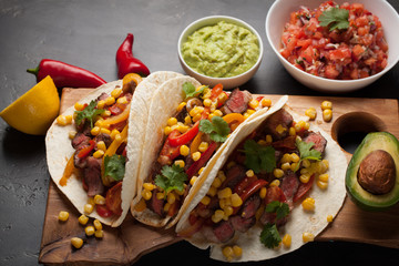 Three Mexican tacos with marbled beef, black Angus and vegetables on wooden Board on a dark stone background. Mexican dish with sauces guacamole and salsa in bowls