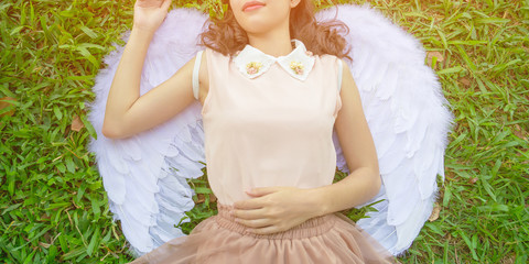 Beautiful young model with angel wings on the grasses background..Girl model wearing a white dress with angel wings and posting hands to heart shape.