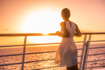 Cruise ship vacation woman travel watching sunset at sea ocean view. Elegant lady in white dress relaxing on deck balcony, luxury holiday destination.