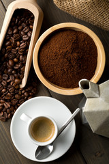 Coffee beans, ground coffee powder and cup of espresso with stovetop coffee maker