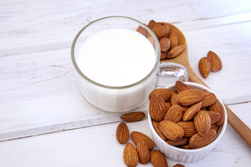 Close up healthy almond milk in drinking glass with seed in white cup and wooden spoon on the white wooden table plate with copy space