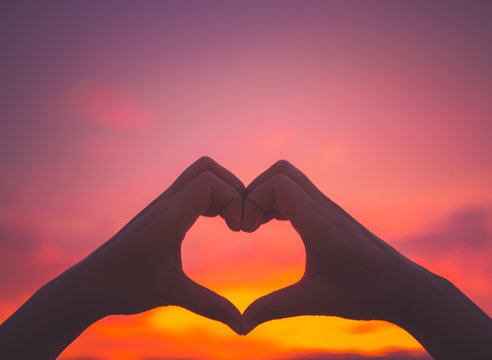 Silhouette woman hands to be heart shape on sunset background. Happy, Love, Valentine's day idea, sign, symbol, concept.