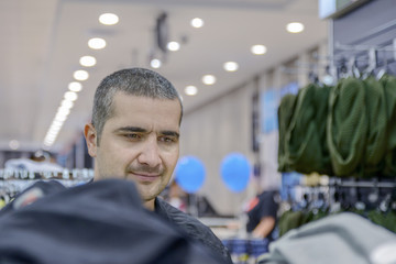 young man with short hair chooses clothes with good mood
