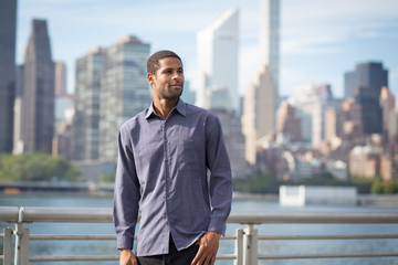 Portrait of young handsome African American man with NYC skyline in the background