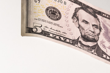 Portrait of Lincoln on a five-dollar bill of the USA on a white background.