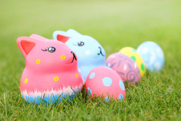 focus colorful rabbit with eggs on amid grass on Easter day