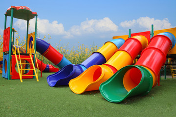 colorful playground park is build happy equipment children on blue sky, flower and grass background
