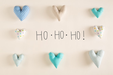 Ho Ho Ho message with blue heart cushions on a white paper background