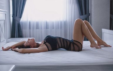 Side view of sexy young woman in black lingerie lying on bed
