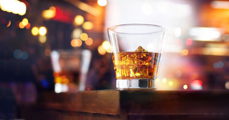 Whiskey glasses drinks with ice cubes on wooden table bar background